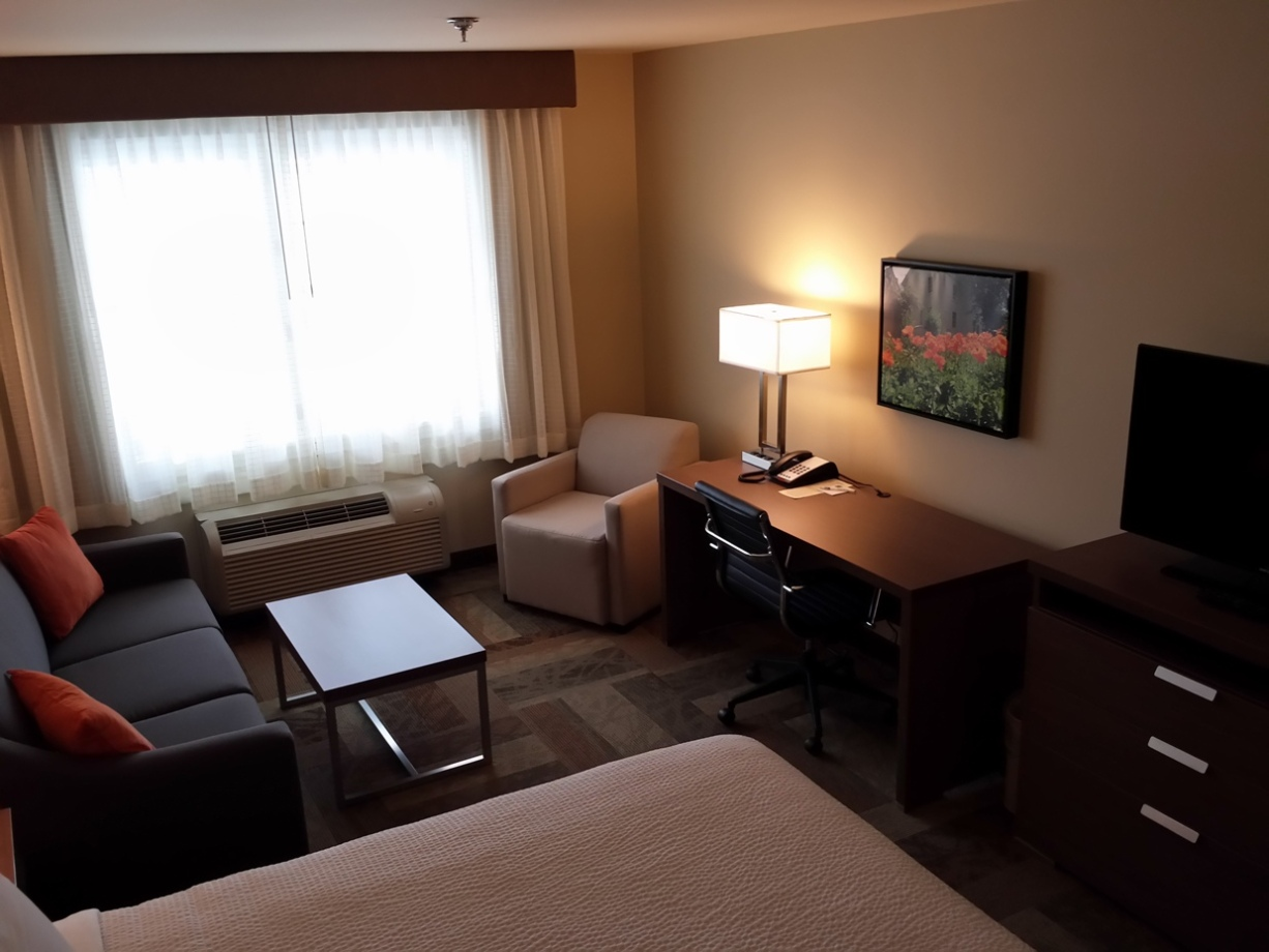 Room with king bed includes desk and flatscreen TV