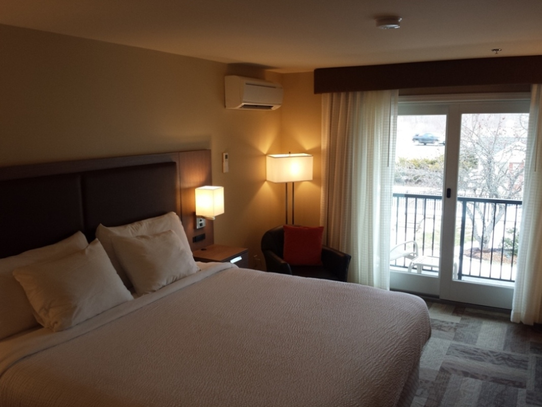 Room with king bed includes desk, flatscreen TV and sliding door to access balcony