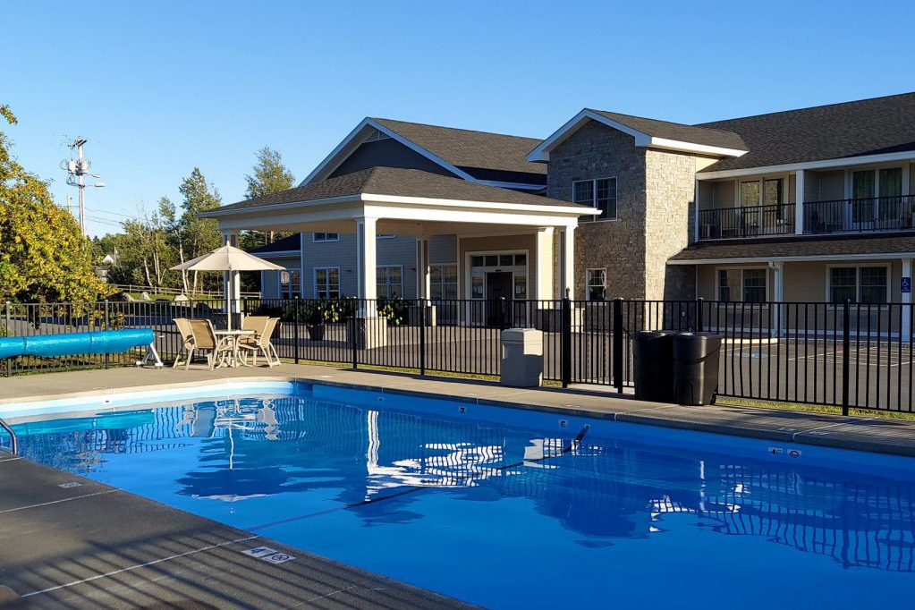 Outdoor pool is located on roadside of property and has lounge seating and tables for guest use