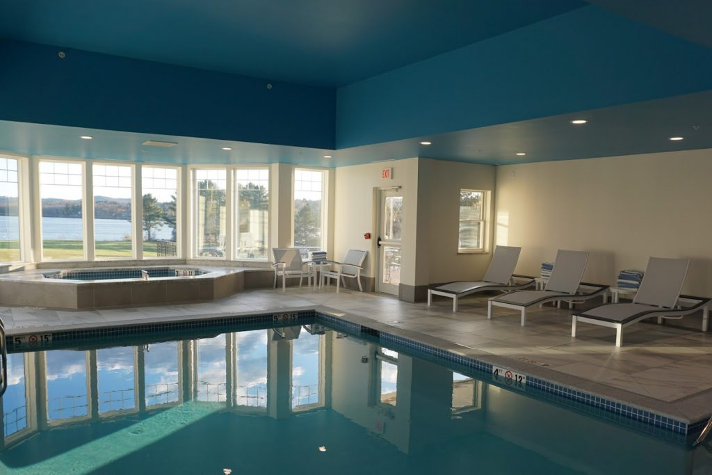Indoor pool and spa includes lounge seating and large windows overlooking the field on the oceanside of the property